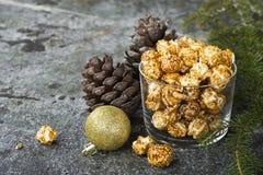Apetyczny złoty karmelu popkorn w papierze paskował filiżanki w nowego roku ` s wnętrzu z jedlinowymi rożkami, nowego roku ` s zł zdjęcie stock