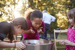 Apfel mit drei jungen Mädchen, der an einer Hinterhofpartei sich ruckartig bewegt stockbilder