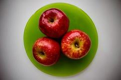 Apfel mit drei Rottönen auf einer grünen Platte Lizenzfreie Stockfotografie