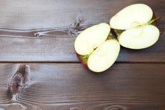 Apfel mit zwei Hälften, Stücke eines roten Apfels auf dem Tisch, rote Äpfel auf einem braunen Hintergrund Lizenzfreie Stockfotografie