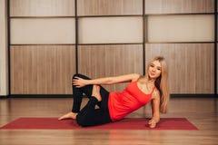 Apfel- und Bandmaß Junge Schönheit tut Yogaübung im modernen Raum Stockbild