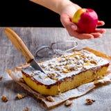 Apfelkuchen, abgewischt mit Puderzucker und Schnitt mit einem Messer Hand Stockfotos