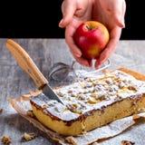Apfelkuchen, abgewischt mit Puderzucker und Schnitt mit einem Messer Hand Stockfotografie