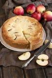 Apfelkuchen auf dem Holztisch mit frischen Äpfeln Lizenzfreie Stockbilder