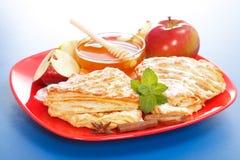 Apfelkuchen auf Platten-, Honig- und Apfelstücken Stockbild