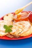 Apfelkuchen auf Platten-, Honig- und Apfelstücken herum Stockbilder