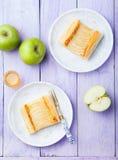 Apfelkuchen, Blätterteigstreifen mit Vanillevanillepudding auf einem hölzernen Hintergrund Lizenzfreie Stockfotos