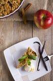 Apfelkuchen mit der Eiscreme, verziert mit Vanille, Minze und Zimt auf hölzernem Hintergrund Ein köstliches Stück des Kuchens mit Stockfoto