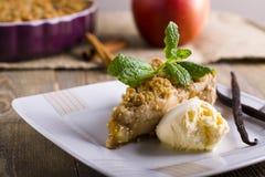 Apfelkuchen mit der Eiscreme, verziert mit Vanille, Minze und Zimt auf hölzernem Hintergrund Ein köstliches Stück des Kuchens mit Stockfotos