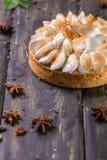 Apfelkuchen mit Meringe- und Kalkschale auf einem hölzernen Stand lizenzfreie stockfotos