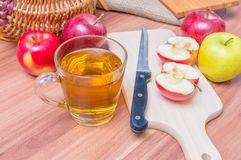 Apfelwein - heißes Apfelgetränk und -äpfel des Alkohols auf Holztisch Stockfotografie
