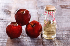 Apfelweinessig und -äpfel über weißem hölzernem Hintergrund Stockfoto
