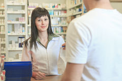 APharmacist helping customer at counter place Royalty Free Stock Image