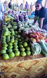 Apia, Samoa - October 27, 2017: Samoan female stall holder at Fugalei fresh produce market with her display of tropical fruit stock photography
