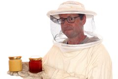 Apiarist with honey glasses in hands. Isolated on white background stock image
