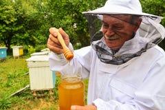 Apiarist mayor que presenta el tarro de miel fresca en colmenar Fotos de archivo