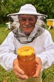 Apiarist mayor que presenta el tarro de miel fresca en colmenar Imagen de archivo