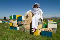 Apiarist watching over his bee hives. Horizontal photo of a beekeeper in white protection suit standing on his bee hives Stock Photography