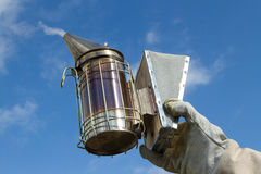 Apiary Smoker. A gloved hand holds a metal bee smoker by the bellows against a blue sky Royalty Free Stock Photos