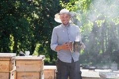 Apicoltore con il fumatore dagli alveari di legno Giovane agricoltore sul lavoro nella sua azienda agricola Fotografia Stock Libera da Diritti