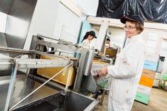 Apicoltore femminile Working On Honey Extraction Plant Fotografie Stock