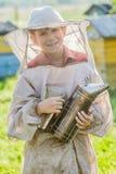 Apicultor joven que comprueba colmenas en yarda de la abeja Imagen de archivo
