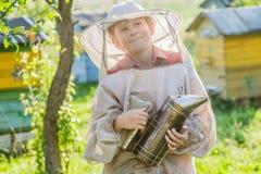 Apicultor joven que usa a un fumador en yarda de la abeja Fotografía de archivo