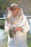 Apicultor mayor experimentado que hace la inspección y el enjambre de abejas Foto de archivo libre de regalías