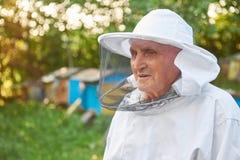 Apicultor mayor que trabaja en su colmenar Fotos de archivo libres de regalías