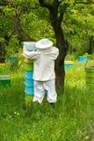 Apicultor que trabaja en sus colmenas en el jardín Foto de archivo