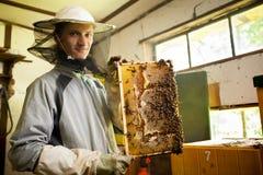 Apicultor que trabaja en un colmenar Foto de archivo libre de regalías