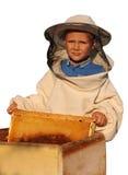 Apicultor un muchacho joven que trabaja en el colmenar Imagen de archivo