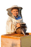 Apicultor un muchacho joven que trabaja en el colmenar Fotos de archivo libres de regalías