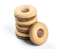 Apilado alrededor de las galletas remató con crema del chocolate sobre el fondo blanco Fotos de archivo