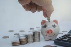 Apile la moneda con descenso de la mano la moneda en la hucha financiero Fotos de archivo libres de regalías