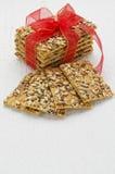 Apile las galletas del cereal atadas con la cinta roja en un tabl de madera blanco foto de archivo