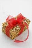 Apile las galletas del cereal atadas con la cinta roja en un tabl de madera blanco foto de archivo libre de regalías