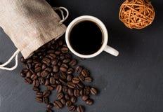 Apile las habas del coffe y la taza de café fresco Fotografía de archivo libre de regalías