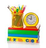 Apile los libros de texto, el sistema de los efectos de escritorio y el despertador aislados en blanco imagen de archivo