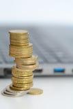Apile o pila de monedas en un teclado del ordenador portátil Imagenes de archivo