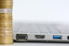 Apile o pila de monedas y de billetes de dólar en un teclado del ordenador portátil Imágenes de archivo libres de regalías