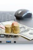 Apile o pila de monedas y de billetes de dólar en un teclado del ordenador portátil Fotos de archivo