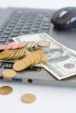 Apile o pila de monedas y de billetes de dólar en un teclado del ordenador portátil Imagen de archivo