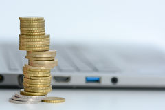 Apile o pila de monedas y de un teclado del ordenador portátil Foto de archivo
