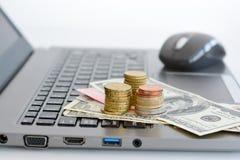 Apile o pila de monedas y de un teclado del ordenador portátil Fotos de archivo