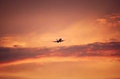 Aplane o vôo em cima do céu vermelho Fotos de Stock