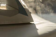 Aplatissez la blanchisserie sur une planche à repasser image stock
