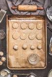 Aplatissez les biscuits avec le fond d'un verre à boire sur le plateau de cuisson, de la préparation sur le fond de table de cuis photographie stock libre de droits