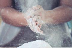 Aplauso de mão da mulher e polvilhar da farinha branca na massa Imagens de Stock