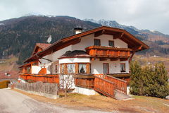 Alpine guest house in Tirol, Austria. Beautiful guest house is in a tipical alpine architectural style. It is located in a village Neder in Austria. The white stock photo